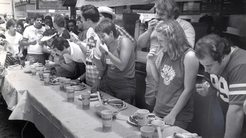 people competing at the first ever major recorded hot dog eating contest