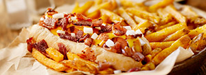 Boost Your Backyard Grill Out With a Bacon Hot Dog Topping Bar